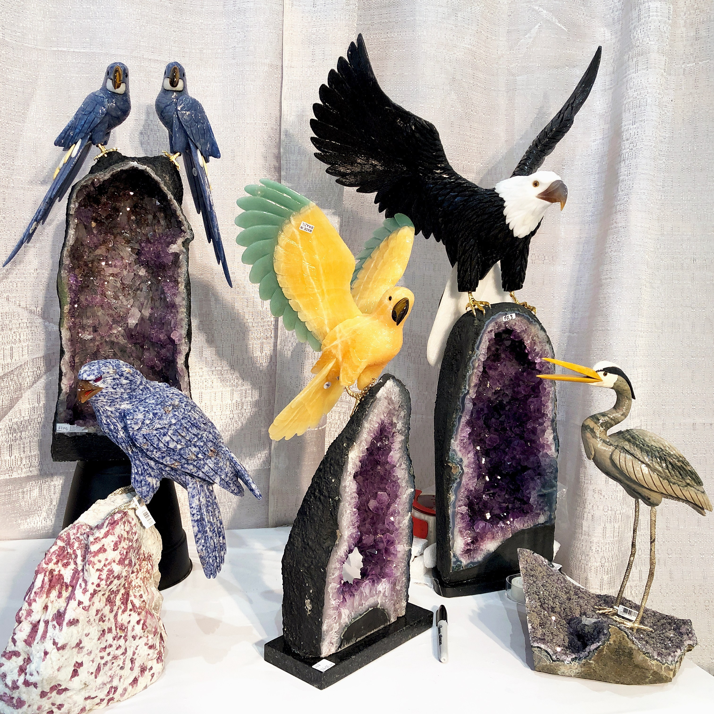 Incredible carved gemstone bird statues from BB Gems, some with amethyst geodes! Spotted at the 2019 AGTA GemFair.