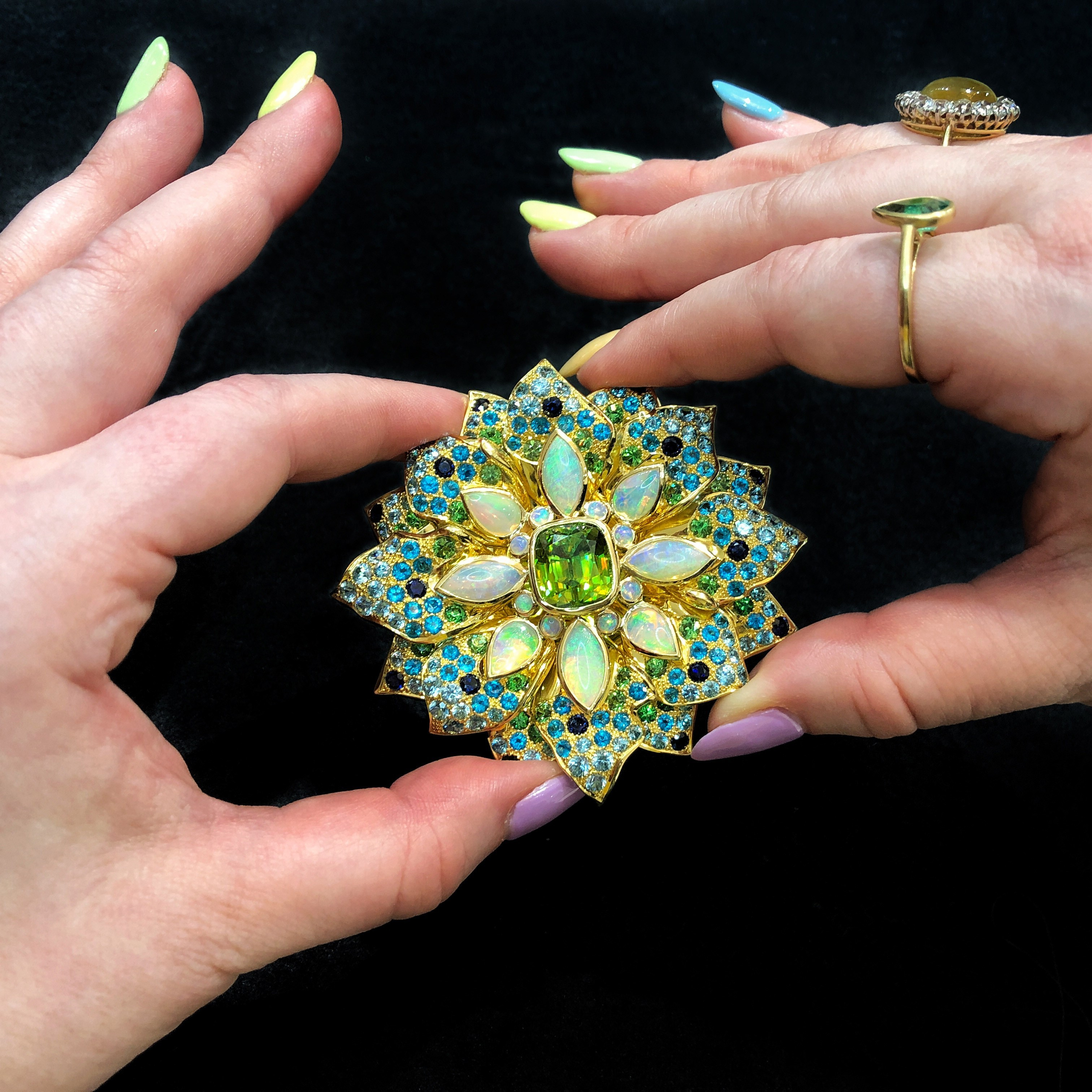 This Paula Crevoshay brooch is inspired by the sea anemone and features sphene, opal, blue zircon, sapphires, tsavorite, and apatite.