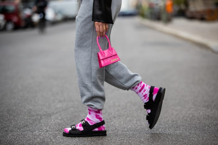 woman-wearing-grey-sweatpants-with-tie-dye-socks-chanel-sandals-pink-mini-jacquemus-bag