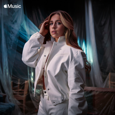 A photo of singer Tate McRae wearing all white and touching her hand to her hair
