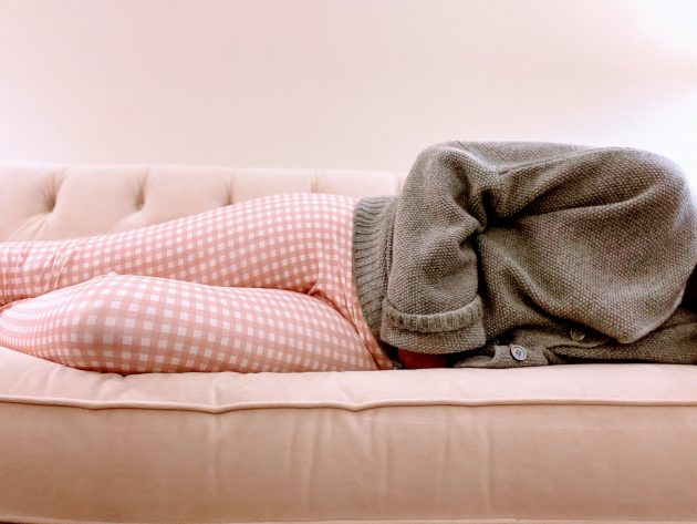 Reasons for a missed period: A woman lies on a sofa clutching her stomach